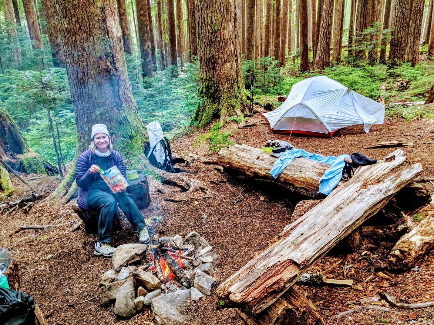 Trisha Wirta eating in front of a fire in her campground with a tent in the background and two logs in the front.