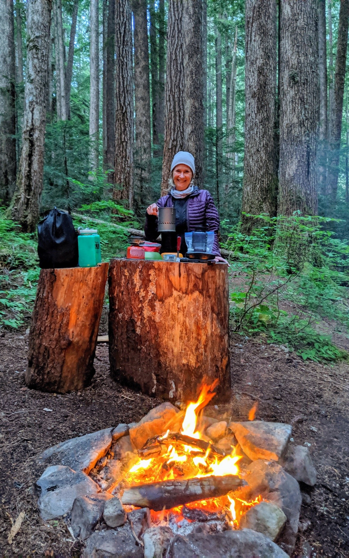Trisha Wirta using two very large stump to lay out her supplies for dinner with a campfire in front of the stumps.