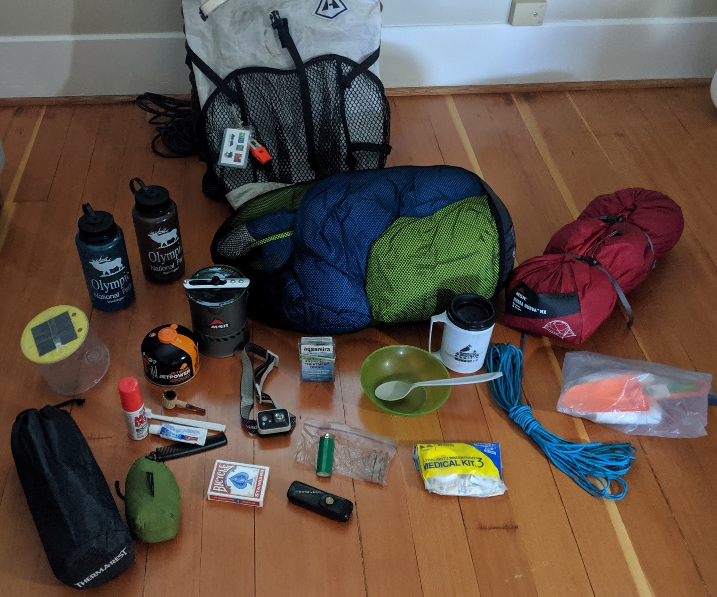 Materials to pack for a hike laid out on the floor.