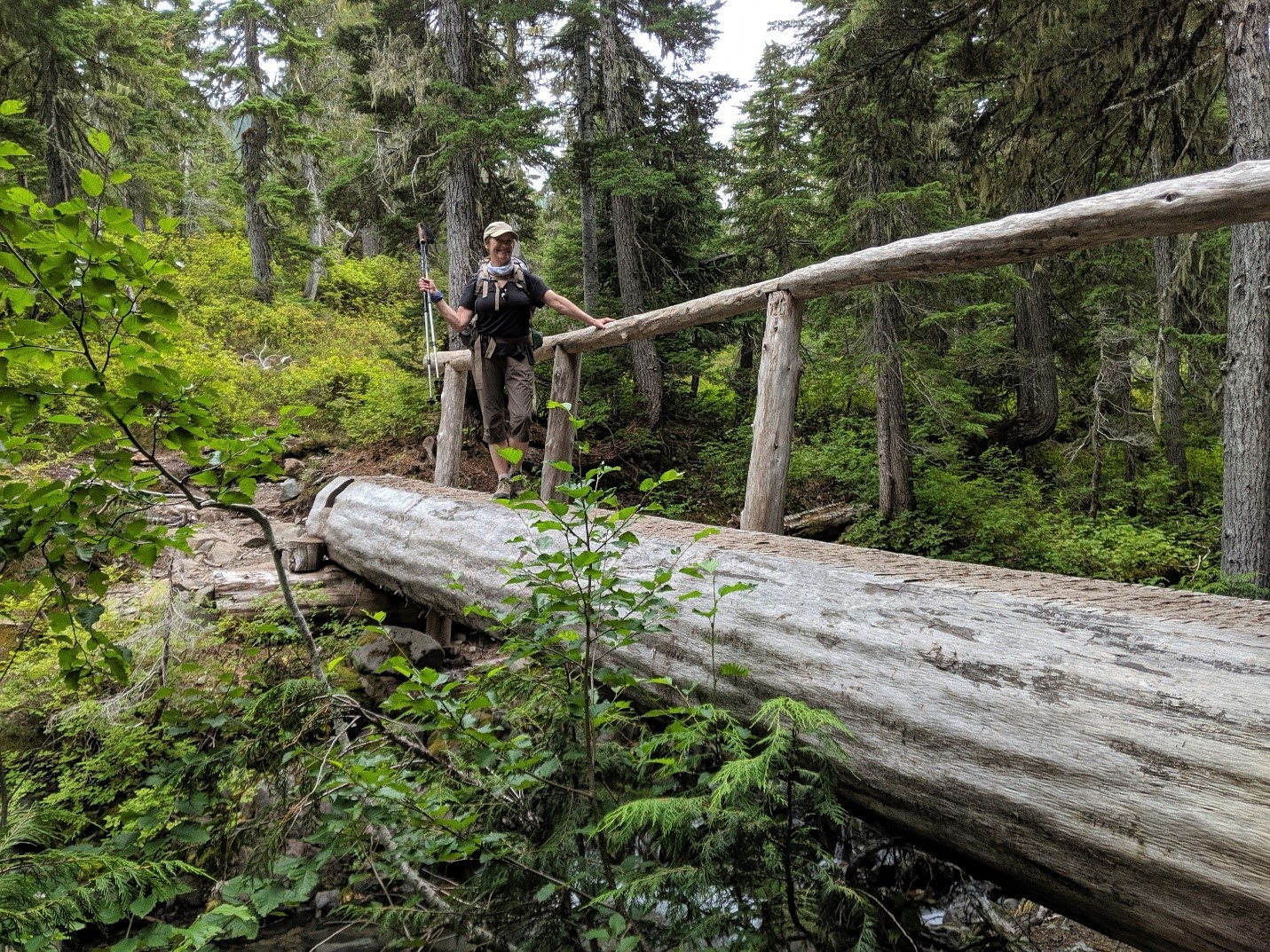 Trisha Wirta crossing a bridge that is just a log with a log made railing