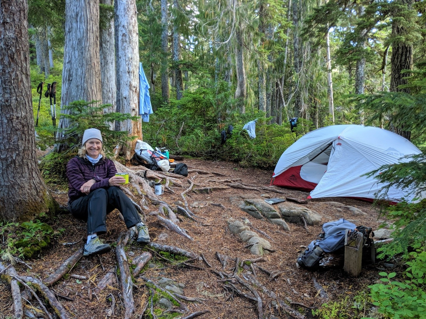 Trisha leaning up against a tree at camp with a tent and pack in the background.